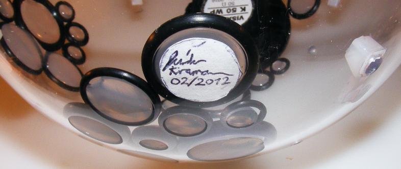 Erst wird der Papierkreis in einen O-Ring in die untere Hälfte der Kugel gelegt, dann wird der O-Ring mit Heißkleber angefüllt.