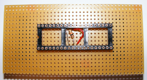 Bestückungsseite einer Platine mit Lochraster und Dreierketten, bestückt mit einer 40-Pin-IC-Fassung für einen ATmega32, einem Widerstand und einer Drahtbrücke.