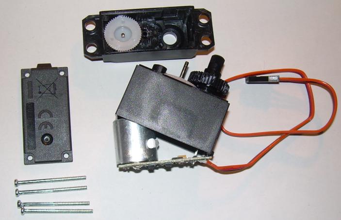 Öffnen der Unterplatte eines Servos mit der Elektronik und vorsichtiges Heraushebeln dieser. Rechts unten sind die Anschlüsse des Potentiometers zu sehen.