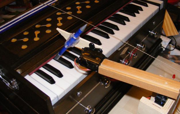 Primitiver Roboterarm spielt Baßmelodie auf einem indischen Harmonium.